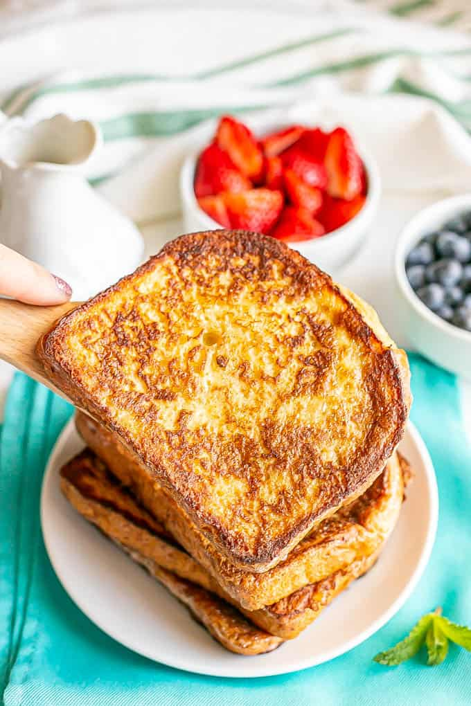 A slice of French toast being added to a stack on a plate