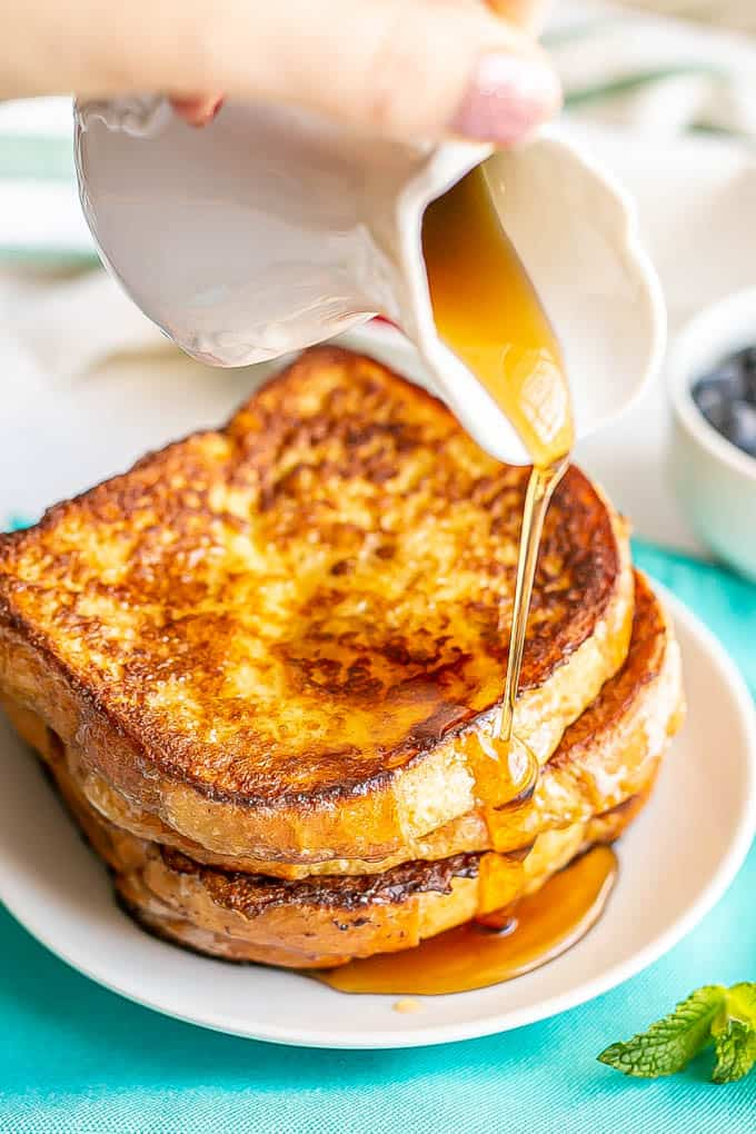 Maple syrup being poured over a stack of homemade easy French toast on a white plate