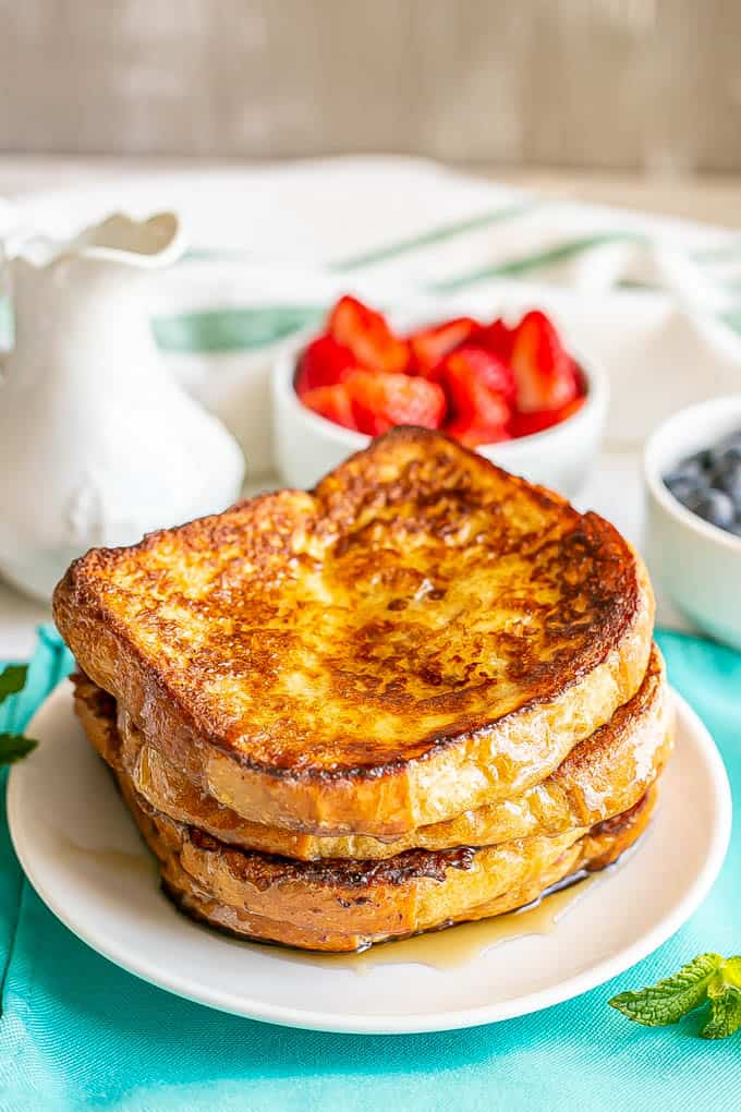 A small white plate with three stacked slices of French toast drizzled with maple syrup with bowls of fresh berries nearby