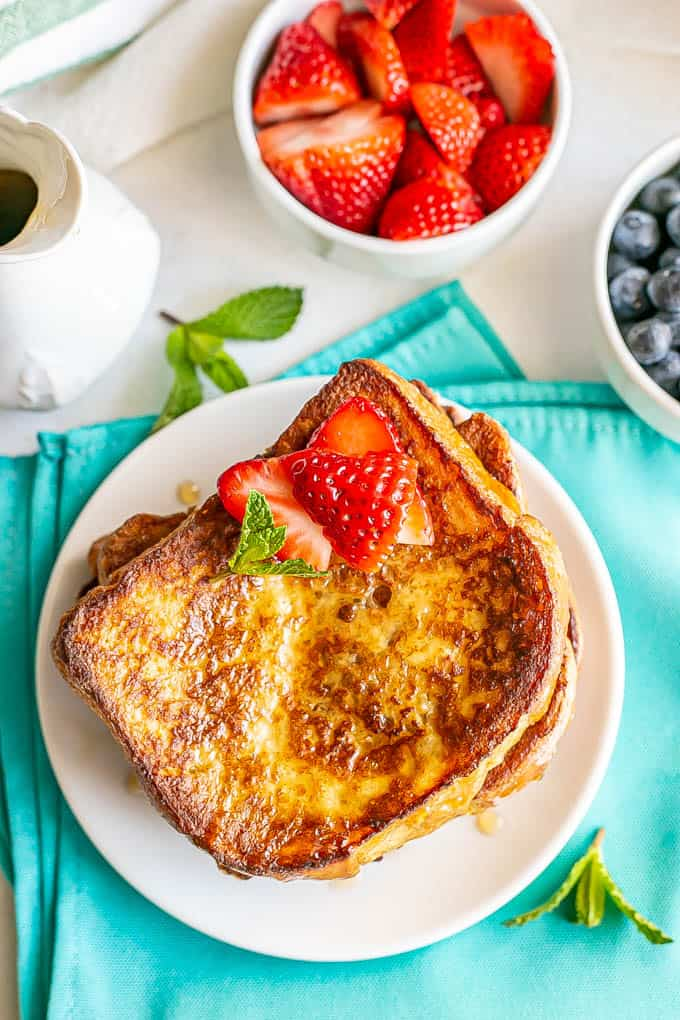 Overheat shot of cooked, browned French toast slices on a white plate with bowls of fresh berries nearby