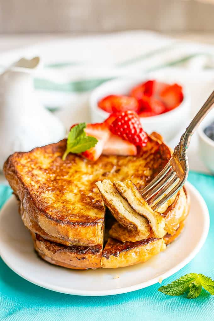 A fork picking up a cut out slice of French toast from a stack on a small white plate with berries and fresh mint nearby
