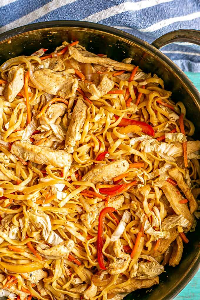 Close up of a large skillet full of chicken lo mein with red peppers, cabbage and carrots
