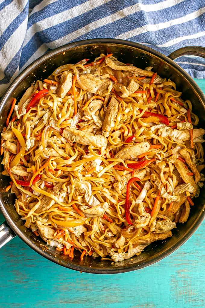 A large skillet full of chicken lo mein with red peppers, cabbage and carrots