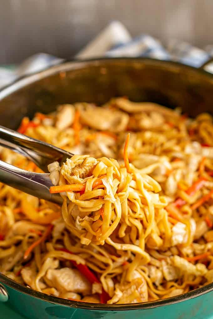 Tongs picking up a tangle of lo mein noodles from a large skillet