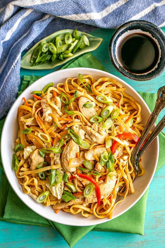 Overhead shot of chicken lo mein served in a shallow white bowl with two forks resting in the bowl and soy sauce and green onions to the side