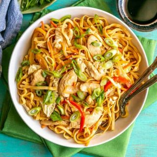 Overhead shot of chicken lo mein served in a shallow white bowl with two forks resting in the bowl and soy sauce to the side