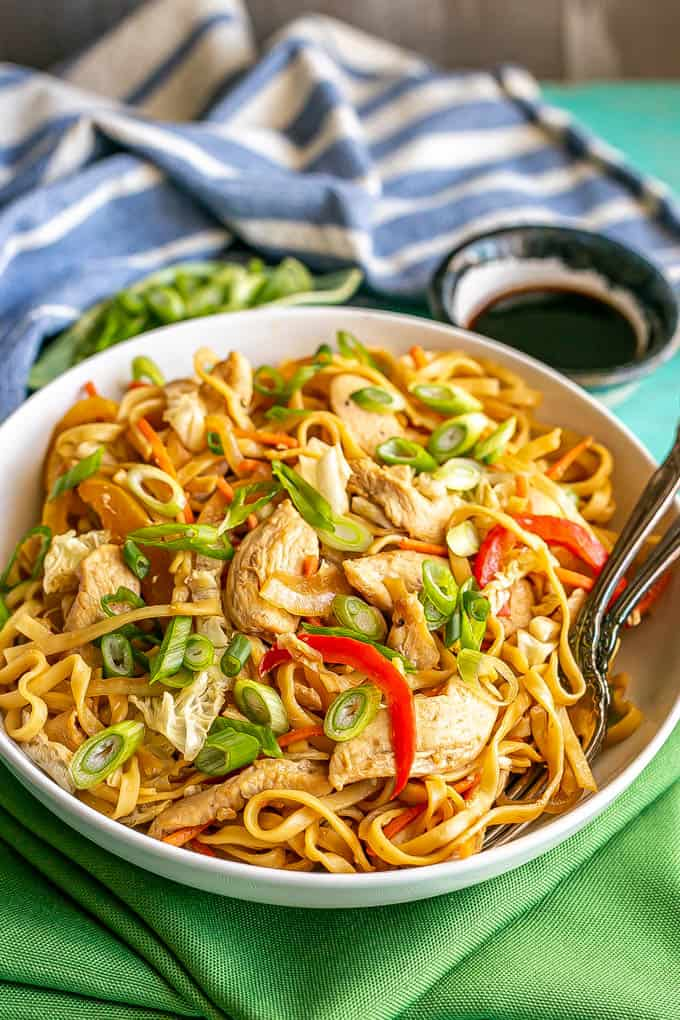 A shallow, wide white bowl full of chicken lo mein topped with sliced green onions