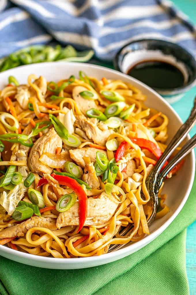 Close up of a shallow, wide white bowl full of chicken lo mein topped with sliced green onions with two forks resting in the bowl