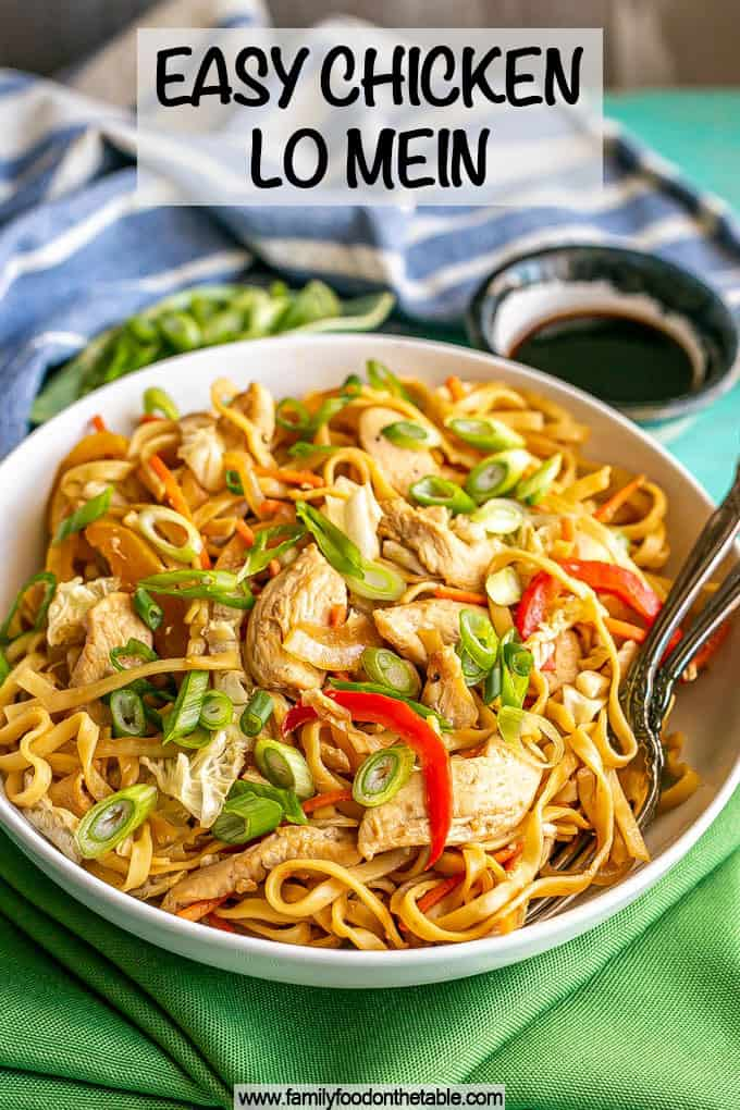 A shallow, wide white bowl full of chicken lo mein topped with sliced green onions and a text overlay on the photo