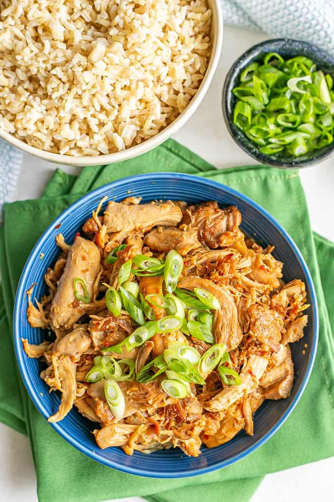 Pressure cooker honey garlic chicken served in a blue bowl with green onions on top and a bowl of rice to the side