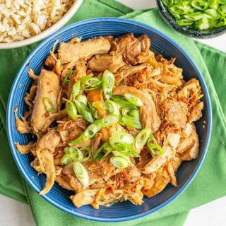 Overhead shot of cooked honey garlic chicken with green onions in a blue bowl set on green napkins