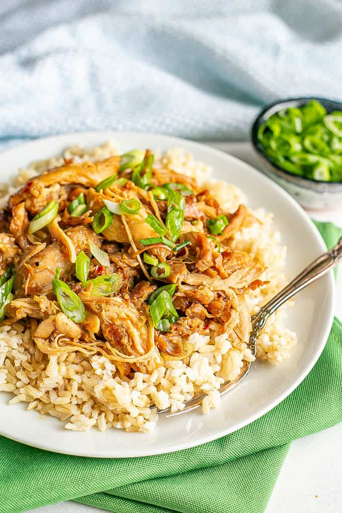 A white plate set on green napkins with brown rice topped with shredded honey garlic chicken and green onions and a fork alongside