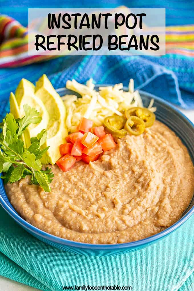 Creamy homemade refried beans in a blue bowl with cilantro, avocado, tomatoes, cheese and pickled jalapenos to the side of the bowl as toppings and a text overlay on the photo