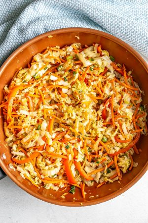 A copper skillet with sauteed cabbage, carrots and veggies