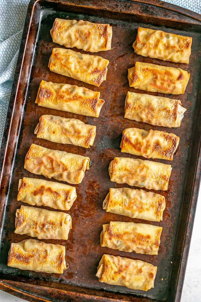 A baking sheet full of wrapped and cooked veggie egg rolls