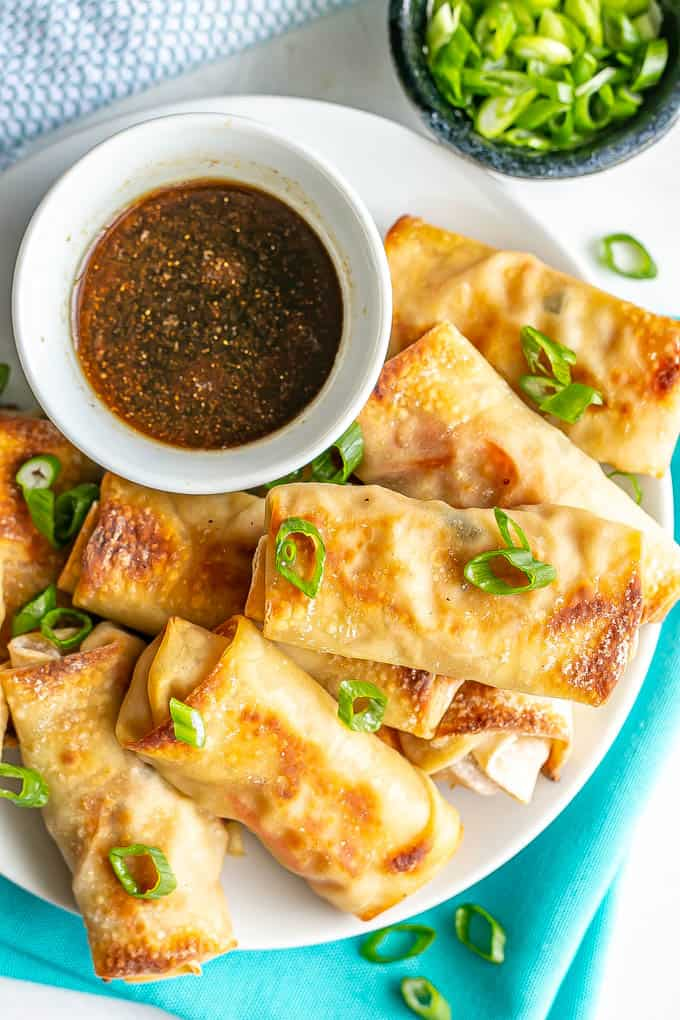 Close up of plate of stacked baked vegetable egg rolls sprinkled with sliced green onions with a small bowl of dipping sauce