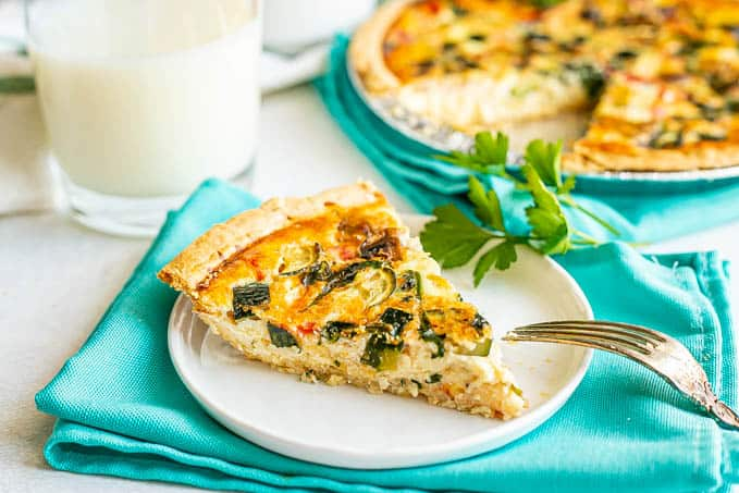 A slice of veggie loaded quiche served on a small white plate set on some turquoise napkins