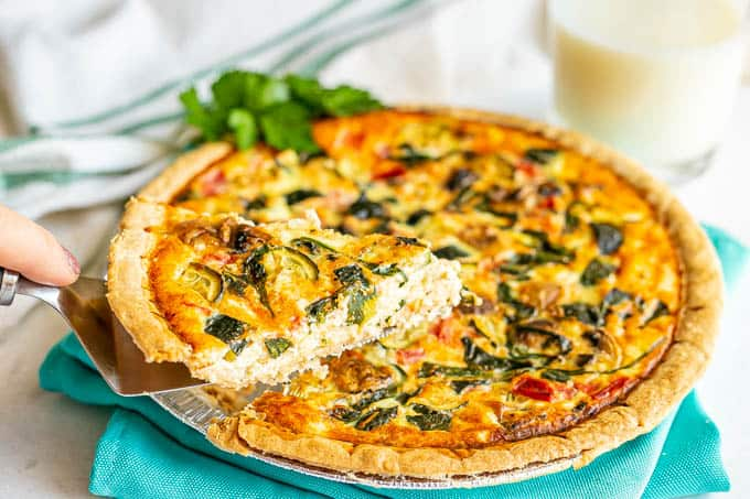 A slice of quiche being lifted from a pie tin with a glass of milk in the background