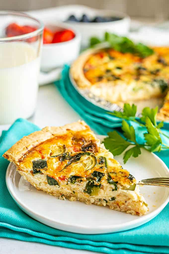 A slice of veggie loaded quiche served on a small white plate set on some turquoise napkins with milk and berries in the background