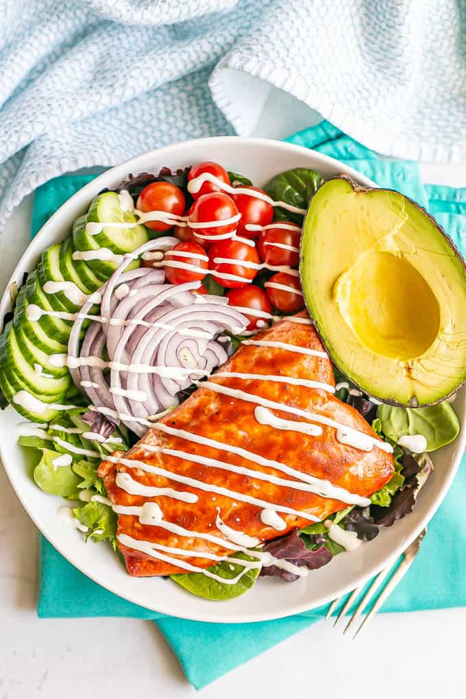 A white salad bowl with mixed greens, tomatoes, cucumbers, red onion, avocado and roasted BBQ salmon