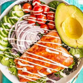 Mixed greens and veggie salad with BBQ salmon, avocado and a creamy dressing in a large white bowl