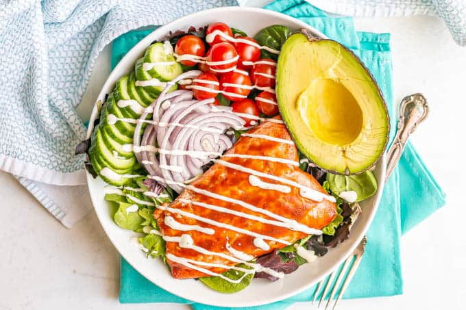 Overhead shot of a salad with cucumbers, tomatoes, red onion, avocado and a filet of BBQ salmon with a drizzle of dressing over everything