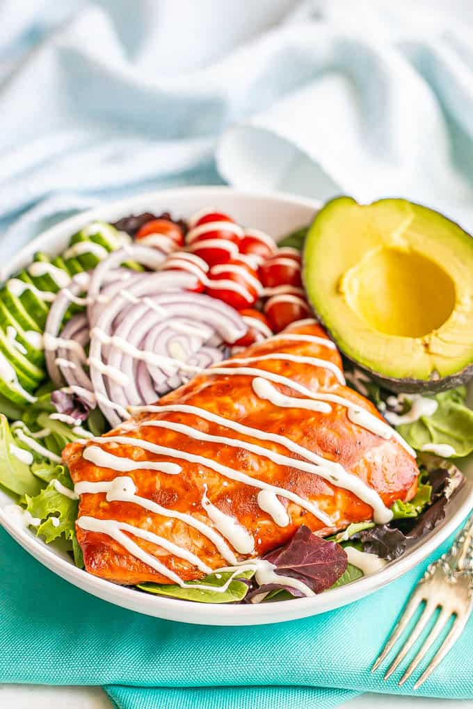 BBQ salmon atop a spring greens and veggie salad in a large white bowl with a half an avocado to the side