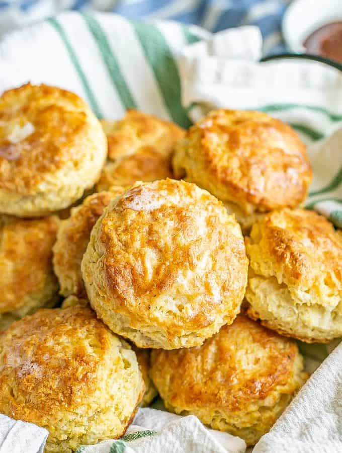 A napkin lined basket with fluffy, browned and buttery homemade biscuits