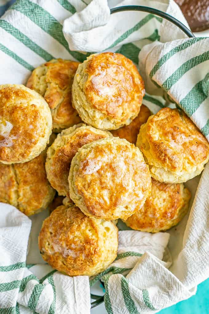 A batch of freshly baked homemade biscuits, brushed with butter, in a green striped napkin lined basket