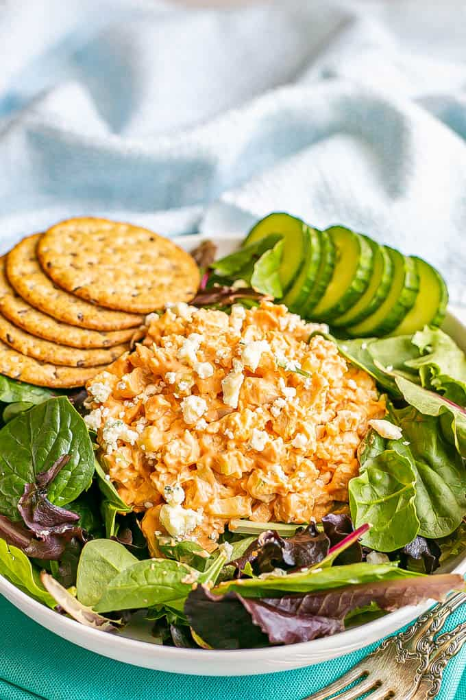 A mound of buffalo chicken salad atop mixed greens in a salad bowl with cucumber slices and whole grain crackers