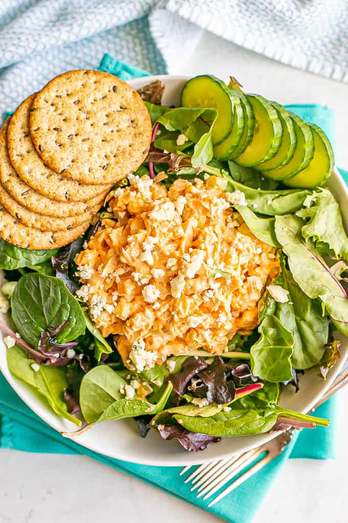 Buffalo chicken salad with blue cheese crumbles served on mixed greens in a large salad bowl with cucumber and crackers to the side