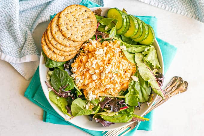 A big scoop of buffalo chicken salad over mixed greens with sliced cumbers and round crackers to the side