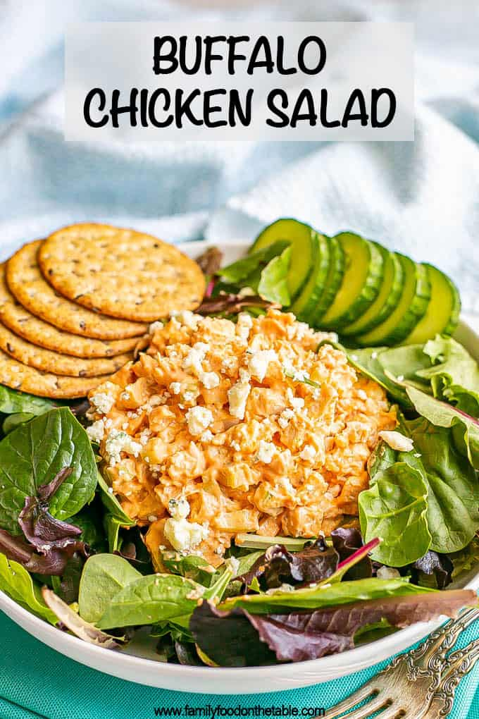 A mound of buffalo chicken salad atop mixed greens in a salad bowl with cucumber slices and whole grain crackers and a text overlay on the photo