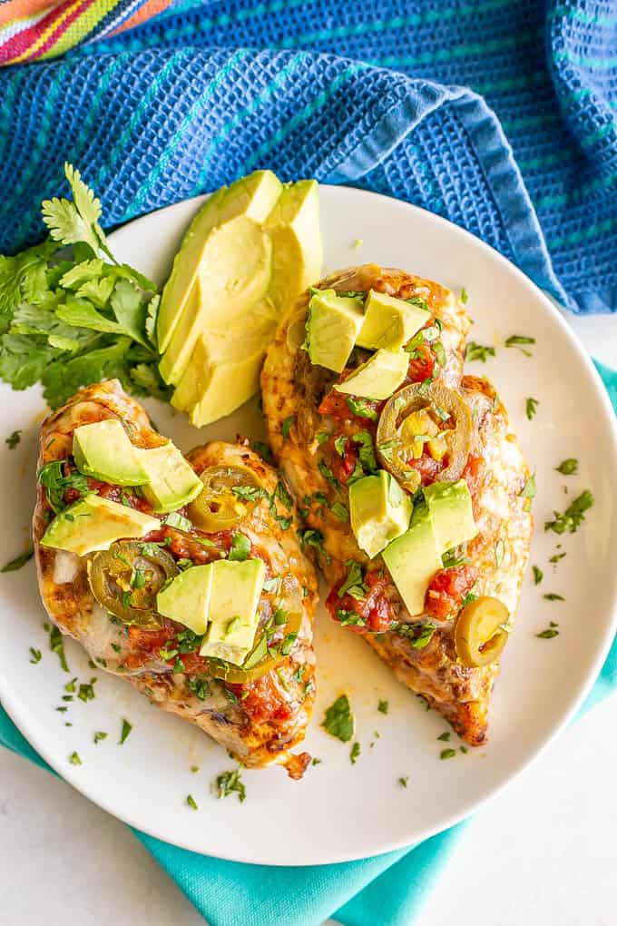 Overhead shot of two grilled chicken breasts seasoned with taco seasoning and topped with melted cheese, salsa, avocado, cilantro and pickled jalapeños
