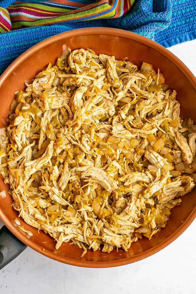 A large copper skillet with a shredded chicken and green chile mixture
