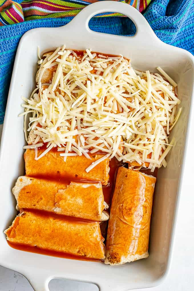 A white baking dish with chicken enchiladas being assembled and topped with cheese before baking