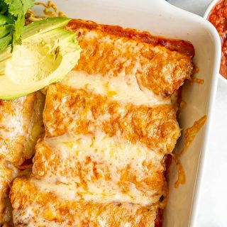 A white pan filled with cheesy chicken enchiladas with avocado slices to the side