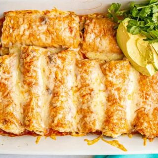 A white pan filled with cheesy chicken enchiladas and topped with cilantro and avocado