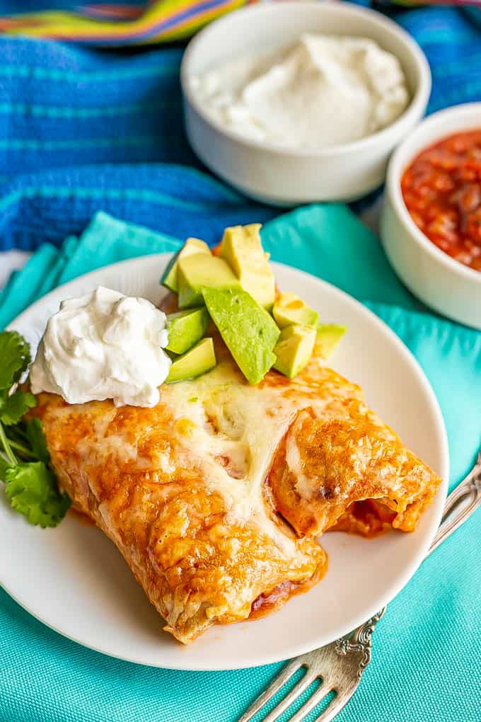 Two cheesy chicken enchiladas served on a small white plate with sour cream, avocado and cilantro on top and salsa and sour cream in bowls in the background
