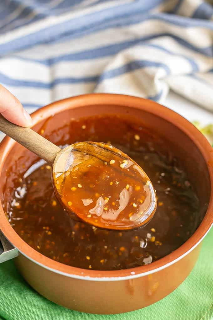 A wooden spoon lifting up some teriyaki sauce from a small copper saucepan