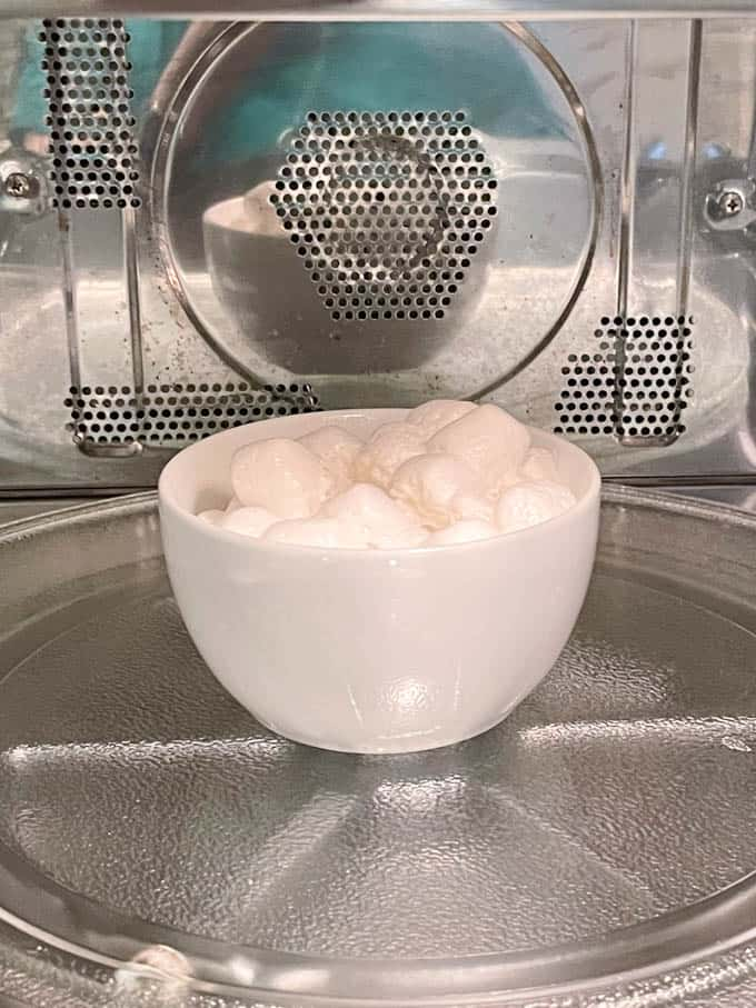 Marshmallows in a small white bowl in the microwave as they are being heated