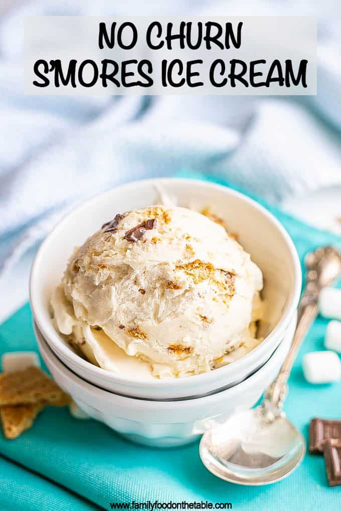 No churn smores ice cream served in a bowl with mini marshmallows, graham crackers and chocolate pieces scattered nearby and a text overlay on the photo