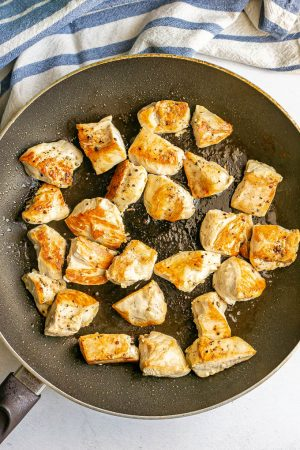 Cubed pieces of chicken breast browned and seared in a large skillet