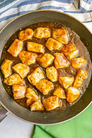 Cubed chicken pieces cooking in teriyaki sauce in a large skillet
