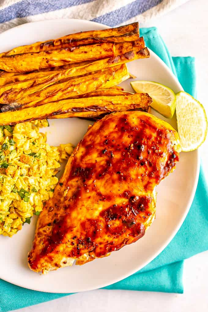 Overhead image of an adobo grilled chicken breast served with sweet potato fries and coleslaw on a plate