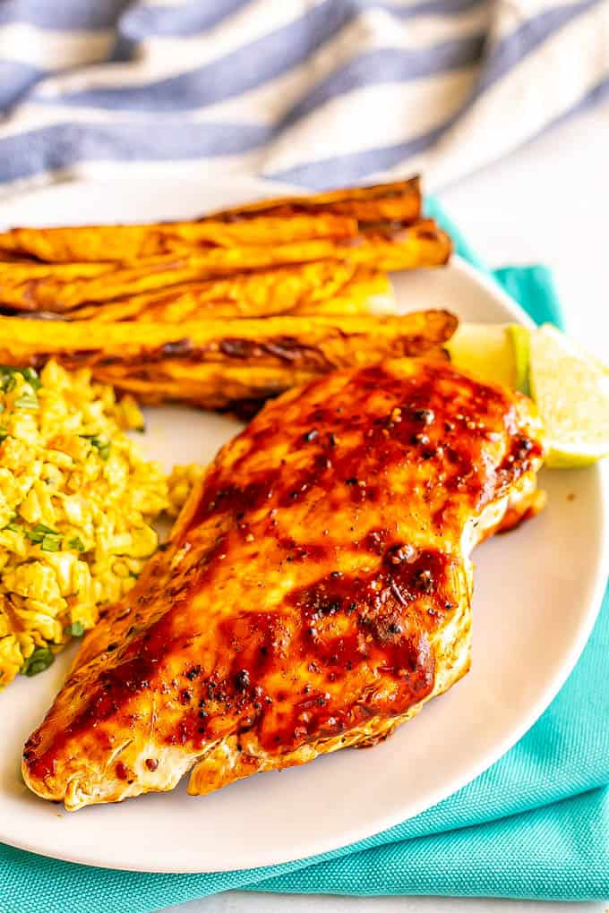 An adobo grilled chicken breast served with sweet potato fries and coleslaw on a plate