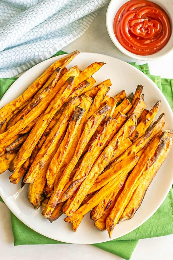 Browned, tender sweet potato fries served on a white plate with a small bowl of ketchup for dipping