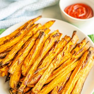 A plate full of cooked, browned Air Fryer sweet potato fries with a small ketchup bowl in the background