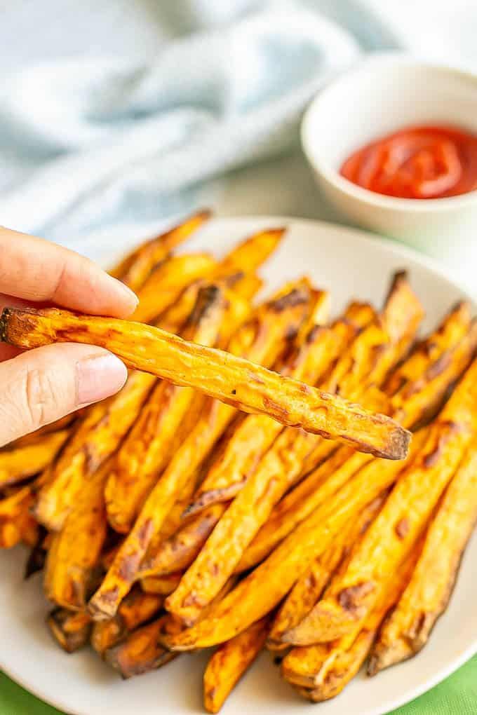 A hand holding up a crispy Air Fryer sweet potato fry from a plate of fries