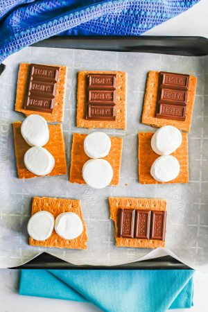 A tray of graham cracker sheets with chocolate and marshmallows on top before being baked in the oven to make s'mores